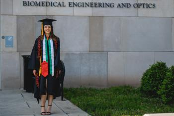 Young woman in graduation robes in front of biomedical engineering and optics building.