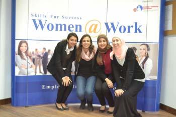 """طالبات أمام لافتة كتب عليها """"مهارات النجاح: النساء في العمل"""""""