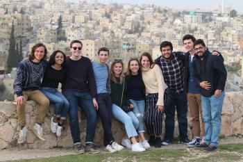 Students posing together in front of a view of Amman