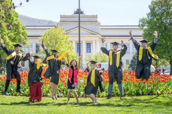 Group of Graduating students jumping in their caps and gowns