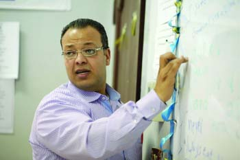 A moroccan teacher is writing something on the board while looking back and speaking to his students