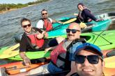 A group of Fulbright Scholars in kayaks, smiling.