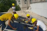 Four students in the Nahdhat Shabab Project wearing hard hats and working on solar panels