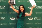 Female student holding up awards in front of Ohio University backdrop