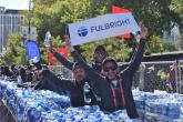 Two male students volunteering and holding up a Fulbright sign