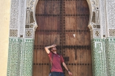 A student posing in front of an ornate door in Morocco
