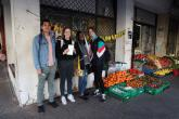 Students pose in front of a hanout with the fruits and vegetables.