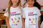 Two young female students in Camp Discovery shirts smile