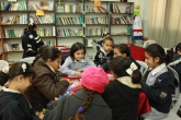 Young female students sit at a table in a library, reading and writing