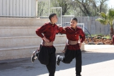 Two young males hold each other's arms while performing a Dabke dance