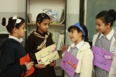 Young female LTD students hold signs with Arabic text written on them while talking to each other