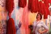 Student standing in Marrakech next to dyed fabric in Morocco