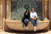 Two students sit on the edge of the decorative fountain at the Hassan II Mosque in Casablanca