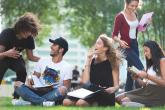 A group of 5 students laughs and talks together while they study outside in the grass.